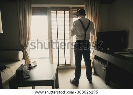 Toned photo of young businessman dressing up at hotel room - stock photo