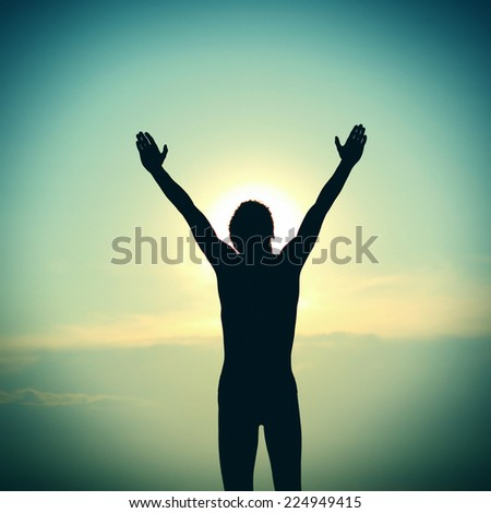 Toned Photo of Young Person Silhouette praying on the Sky Background - stock photo