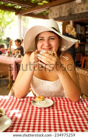 Toned photo of young woman drinking tea at cafe at sunny morning - stock photo