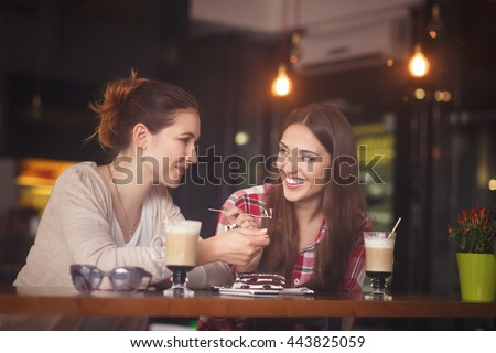 Toned picture of best friends having date in cafe or restaurant. Beautiful girls talking or communicating while drinking coffee. - stock photo