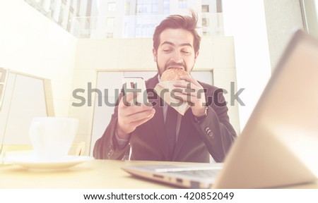 Toned picture of businessman eating hamburger and using mobile or smart phone while sitting in front of laptop computer. - stock photo