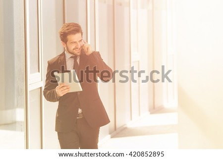 Toned picture of businessman in black suit speaking over mobile or smart phone with business partners. Handsome man hurrying to work. - stock photo
