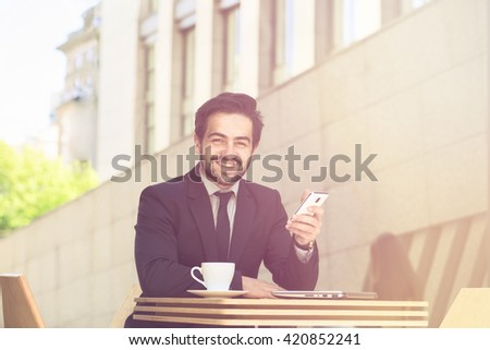 Toned picture of businessman smiling while sitting in restaurant or cafe and working. Freelance man in black suit using mobile or smart phone.