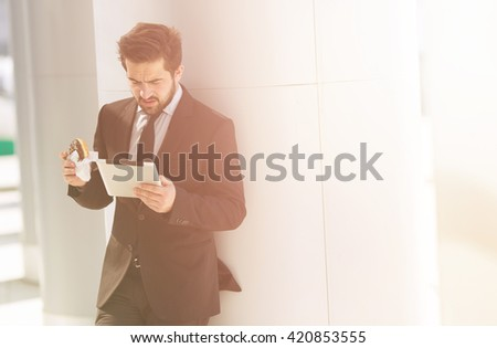 Toned picture of businessman standing near office building and looking at tablet PC. Handsome man eating junk food on street. - stock photo
