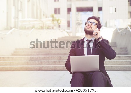 Toned picture of executive businessman speaking over mobile or smart phone, working on his laptop computer and looking at sky or just upwards. - stock photo