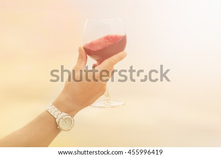 Toned picture of glass with old red wine in sommelier's hand. Red wine is tasted by sommelier isolated on blue sky background. - stock photo