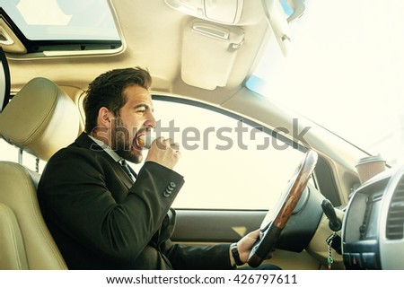 Toned picture of handsome businessman eating junk food while driving to work. Freelance man hurrying in morning to do many things. - stock photo