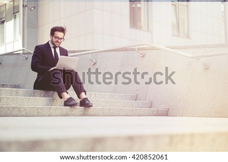 Toned picture of handsome businessman in glasses working on his laptop computer while resting in city centre. Freelance man typing something in his document. - stock photo