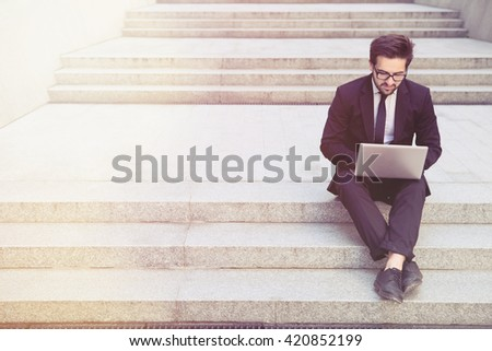 Toned picture of handsome businessman using laptop computer while sitting on stairs in city centre. Executive freelancer in black business suit and glasses.