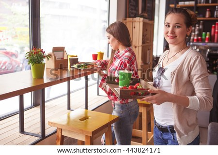 Toned picture of pretty ladies spending free time in cafe or restaurant. Beautiful women about to drink coffee, eat sandwiches, snacks or cakes. - stock photo