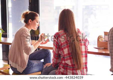 Toned picture of pretty women eating sandwiches and drinking coffee during break. Ladies spending time in cafe or restaurant. - stock photo