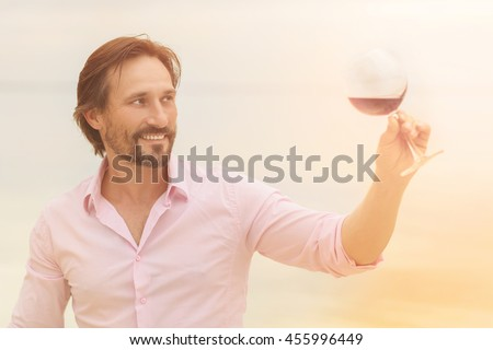 Toned picture of professional sommelier tasting red wine in glass. Happy smiling man is satisfied by taste of red wine isolated on sea. - stock photo