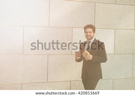 Toned picture of smiling businessman eating junk food and drinkig cupof tea or coffee while walking to office along street. - stock photo