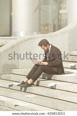 Toned picture of young businessman using laptop computer in city center and working upon business projects on street. Freelance concept. - stock photo