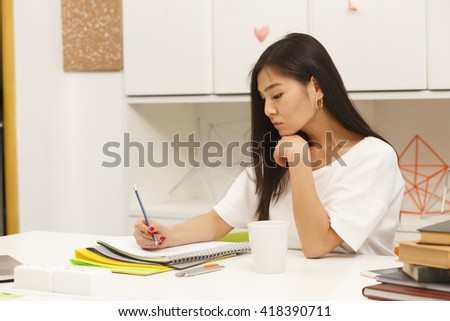 Toned Portrait of Asian student writing something in her exercise-book while sitting in library and preparing for lessons, classes or exams. - stock photo
