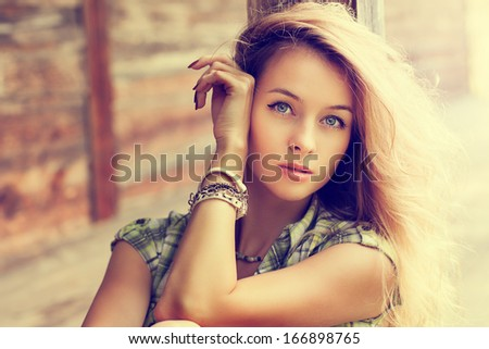 Toned Portrait of Beautiful Blonde Woman on Wooden Background - stock photo