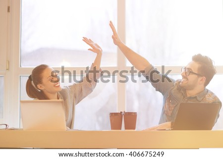 Toned Portrait of freelance man and woman playing during their break. People doing high-five while working on laptop computers. - stock photo