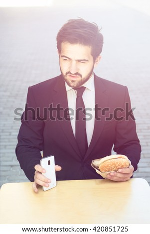 Toned portrait of handsome businessman eating junk food and holding mobile or smart phone while having break in cafe during his work. - stock photo