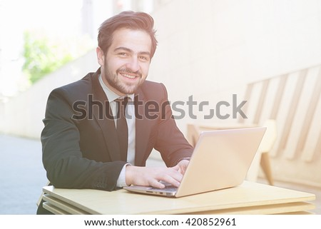 Toned portrait of handsome businessman sitting in cafe or restaurant and working on laptop computer upon different business projects and strategies. - stock photo