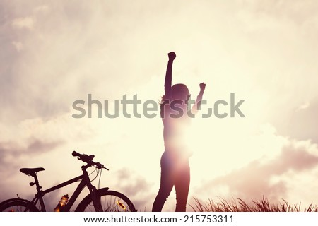 Toned portrait of young woman with raised hands over sunbeams - stock photo