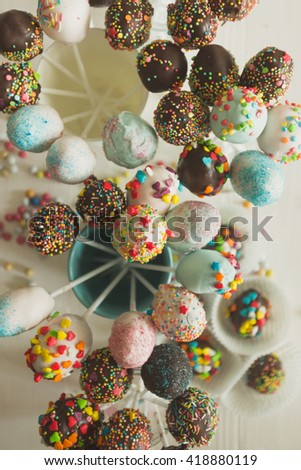 Toned top view shot of colorful pop cake against white wooden background - stock photo
