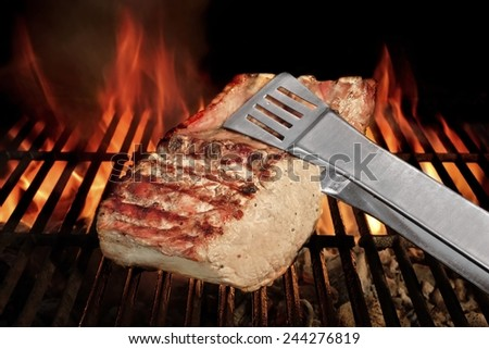 Tongs Holding Grilled Pork Ribs. Hot Flaming BBQ Grill on the Background - stock photo