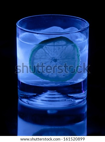 Tonic water in highball tumbler glows blue in ultraviolet light - stock photo
