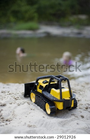 Tonka road grader in sand with children playing in water in background - stock photo