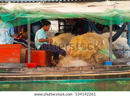 Tonle Sap Lake Siem Reap, Cambodia - OCTOBER 13, 2012: The man and his family weaves a fishing net on the boat house. The life of the local residents