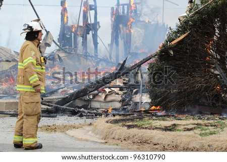 TONTITOWN, AR - FEBRUARY 4: A fireman watches as a fire completes it's awful destruction after a control burn exercise on February 4, 2012 in Tontitown, AR.  The exercise was open to the public. - stock photo