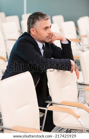 Too boring conference. Bored mature man in formalwear holding hand on chin while sitting on the chair in empty conference hall  - stock photo