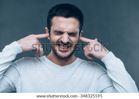 Too loud sound! Frustrated young man expressing negativity while covering ears with hands and standing against grey background - stock photo