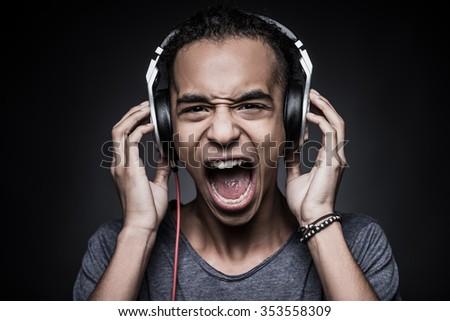 Too loud sound. Furious young African man adjusting headphones and looking at camera with mouth open while standing against black background - stock photo