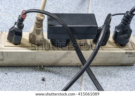 Too many plugs in a dirty socket on the floor. Danger of using old socket and too much electricity