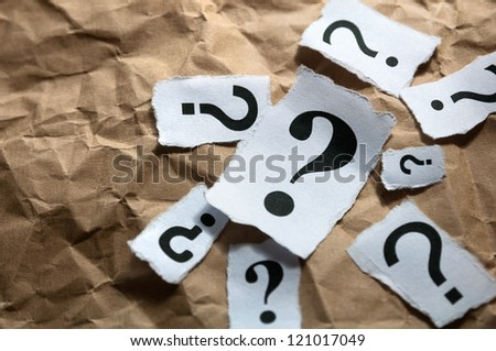 Too many question marks on crumpled paper - stock photo