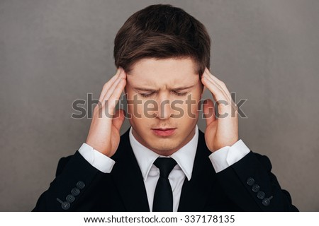 Too much stress. Frustrated young man in formalwear touching head with hands and keeping eyes closed while standing against grey background
