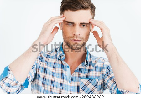 Too much stress. Frustrated young man touching head with fingers and looking at camera while standing against white background - stock photo