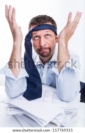 Too much work. Portrait of desperate businessman sitting at office desk full with papers. - stock photo