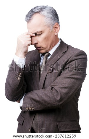 Too stressful day. Frustrated mature man in formalwear touching head with fingers and keeping eyes closed while standing against white background - stock photo