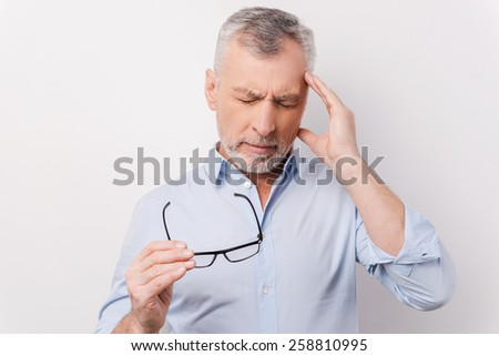 Too stressful day. Frustrated senior man in shirt touching head with fingers and keeping eyes closed while standing against white background - stock photo