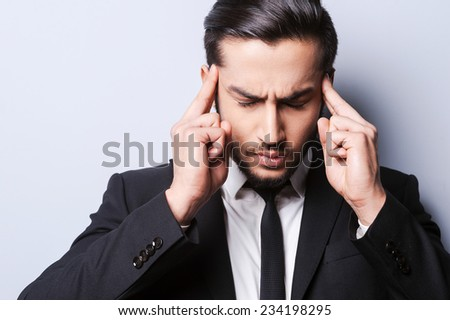 Too stressful day. Frustrated young man in formalwear touching head with fingers and keeping eyes closed while standing against grey background - stock photo