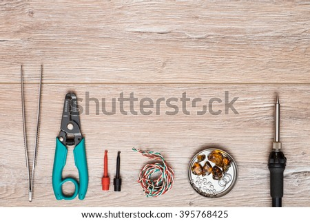 Tool kit for soldering on a wooden table. Electric soldering iron, tweezers, clips, stripping tool, solder and rosin in a can. - stock photo