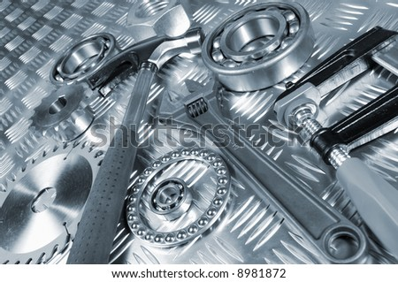 tools and mechanical parts against blue toned steel background