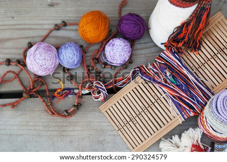 tools and thread for weaving on a wooden background top view - stock photo