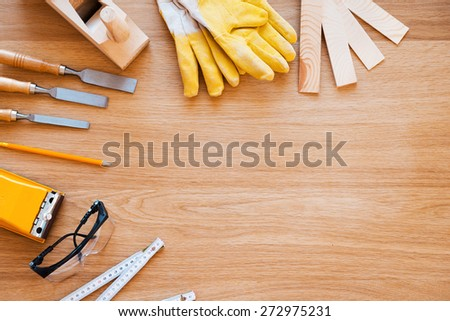 Tools for carpenter. Top view of diverse working tools for wood industry laying on the wood grain - stock photo