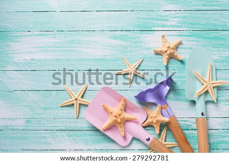 Tools for children for playing in sand  and sea object on turquoise  painted wooden planks. Place for text. Vacation, holiday, summer background.  - stock photo