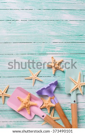 Tools for children for playing in sand  and sea object on turquoise  painted wooden planks. Place for text.  - stock photo