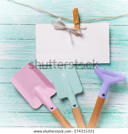 Tools for children for playing in sand and tag on clothes line on turquoise  painted wooden planks. Place for text. Vacation, holiday, summer background. Square image.  - stock photo