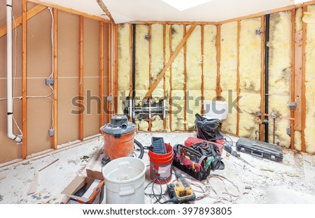 Tools for demolishing and cleaning up the debris from a master bathroom to be remodeled. Walls torn back to studs - stock photo