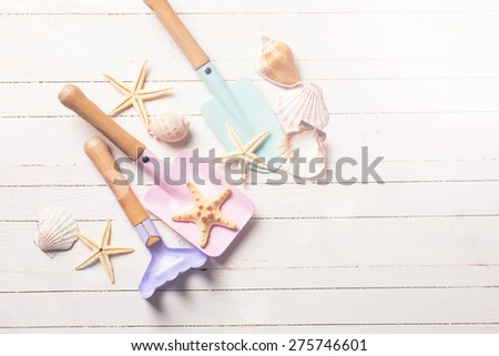 Tools for kids for playing in sand and sea object  in ray of light on white  painted wooden background. Place for text. Vacation  background. - stock photo